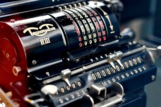 antique calculating machine with rows of number display dials and thousands etc. markers